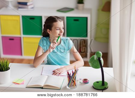 people, children, education and learning concept - happy girl with book and notebook looking through window at home