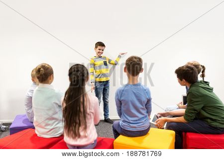 education, elementary school, learning and people concept - happy student boy showing something at white wall