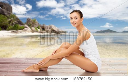 beauty, people and bodycare concept - beautiful woman touching her smooth bare legs over exotic beach background