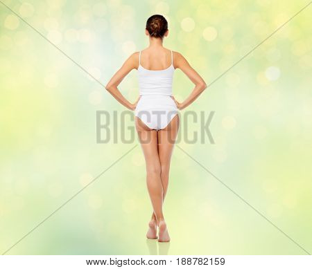 beauty, people and bodycare concept - beautiful young woman in white underwear from back over summer green lights background