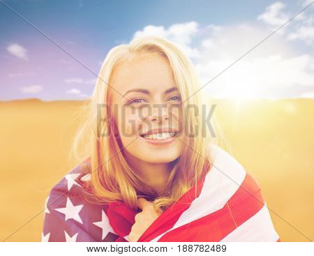 country, patriotism, independence day and people concept - happy smiling young woman wrapped into national american flag on cereal field