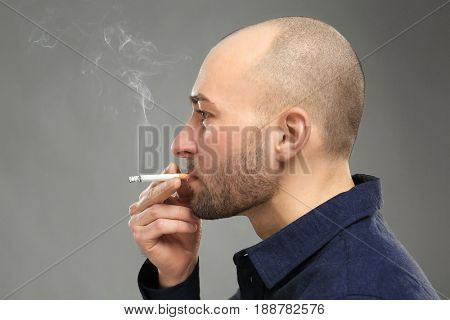 Handsome man smoking cigarette on grey background