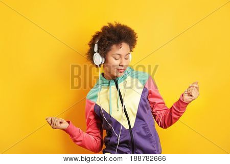 Beautiful African girl with earphones on yellow background