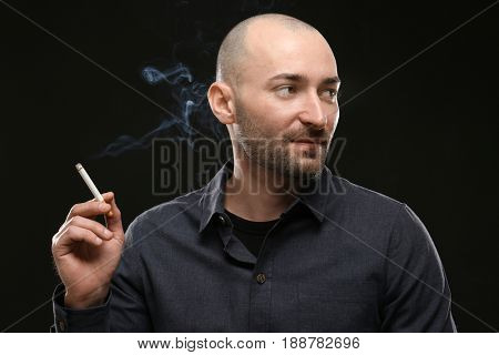 Handsome man smoking cigarette on dark background