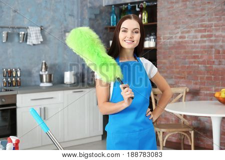 Beautiful woman with duster at home