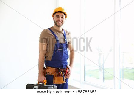 Young smiling electrician holding toolbox and standing near big window