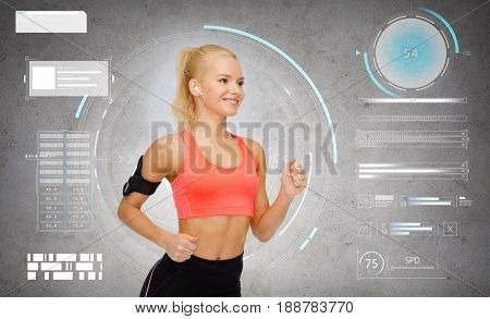 sport, exercise, technology, internet and healthcare - smiling sporty woman running and listening to music from smartphone in armband over gray concrete background