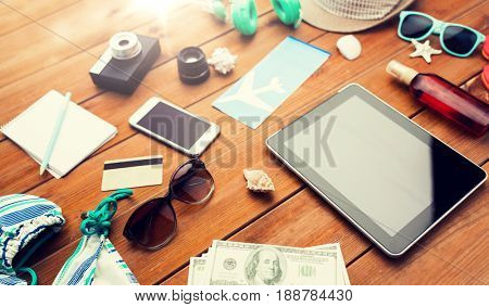 vacation, tourism, technology and objects concept - close up of tablet pc computer, dollar money and travel stuff