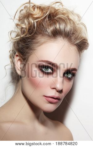Young beautiful woman with smoky eyes and prom hairdo
