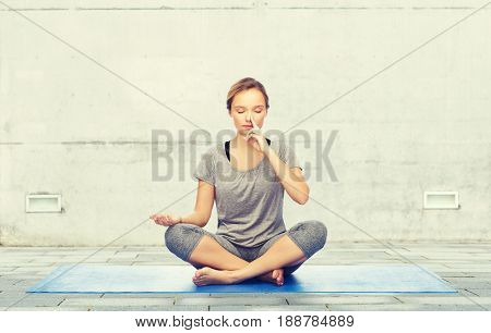 fitness, sport, people and healthy lifestyle concept - woman making yoga meditation in lotus pose on mat over urban street background