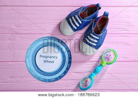 Pregnancy wheel with baby booties on wooden background