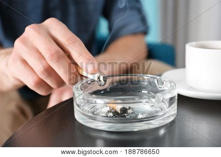 Male hand with cigarette over ashtray on table, closeup