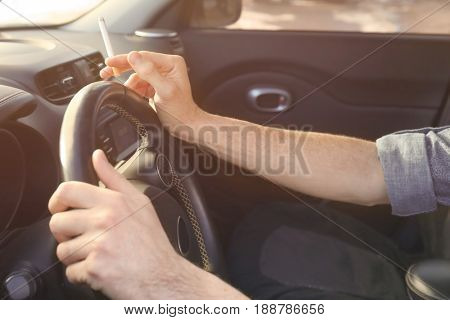 Male hands with cigarette on steering wheel