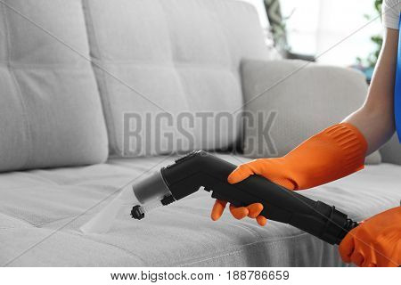 Female hands cleaning couch with vacuum cleaner, closeup