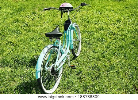 Bicycle with helmet on green grass in park
