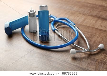 Asthma inhalers with stethoscope on wooden table
