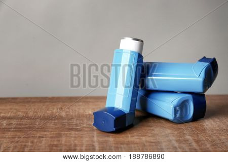 Asthma inhalers on wooden table