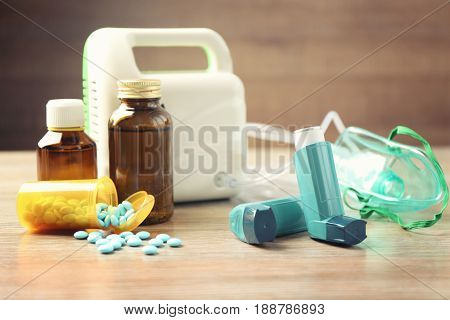 Asthma inhalers, medicines and nebuliser on wooden table