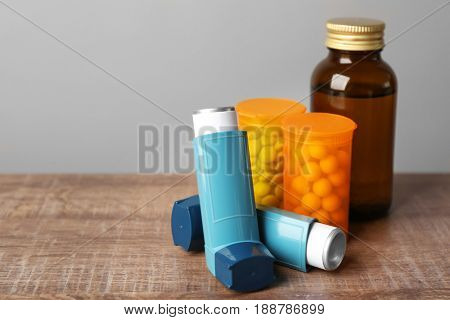 Asthma inhalers with medicines on wooden table