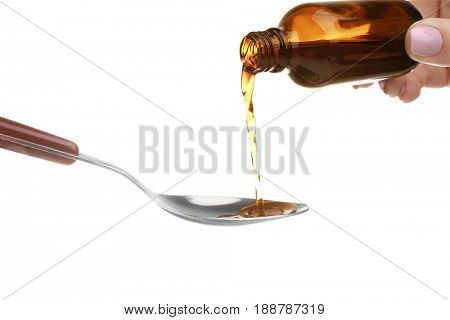 Pouring cough syrup into spoon on white background