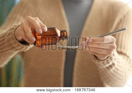 Woman pouring cough syrup into spoon, closeup