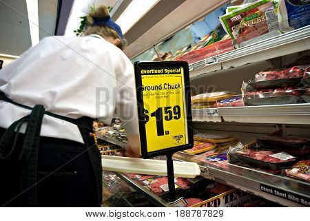 SACRAMENTO, CALIFORNIA, USA - November 3, 2009: Grocery store employee adds packages of hamburger to the meat cold case