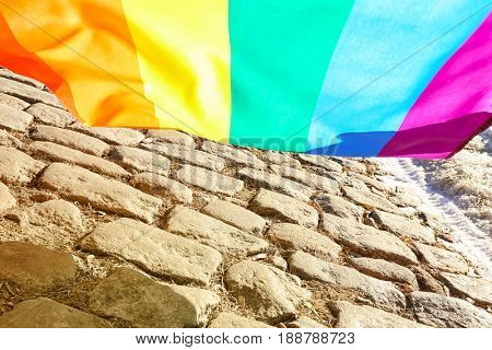Gay flag above stone pavement. Concept of sexual minority