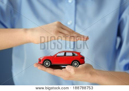 Travel insurance concept. Woman holding toy car