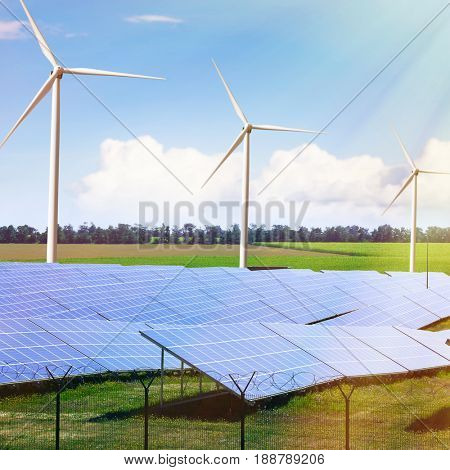 Solar panels and wind generators in field. Concept of renewable energy resources