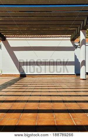 Terrace with shadows from the pergola. Mijas is a village. Andalusia, Spain
