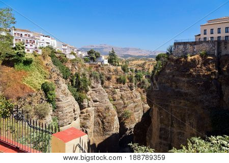 View of the buildings standing on the edge of a cliff in Ronda town, Spain