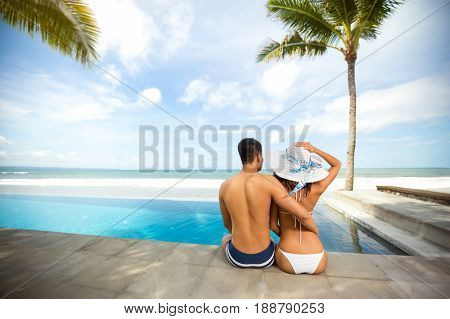 Affectionate couple relaxing in summer vacation, back view