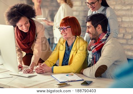 Female Afro-American manager with smile employees looking at computer