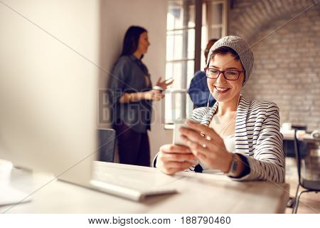 Smiling woman looking at cell phone on pause in business company