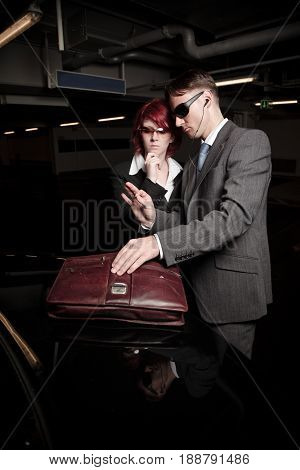 mafiosi couple checking a briefcase at the back of their black limo in a parking garage