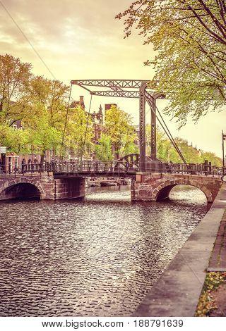 Old drawbridge in Amsterdam city over river Amstel Netherlands. Evening landscape Holland.