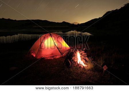 campfire near an illuminated tent on Biviere Lake in Nebrodi Park, Sicily