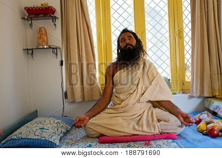 LAXMAN JHULA, INDIA - APRIL 20, 2017: A Hindu swami sitting sitting in meditation in a room in Laxman Jhula on the 20th april 2017 in India