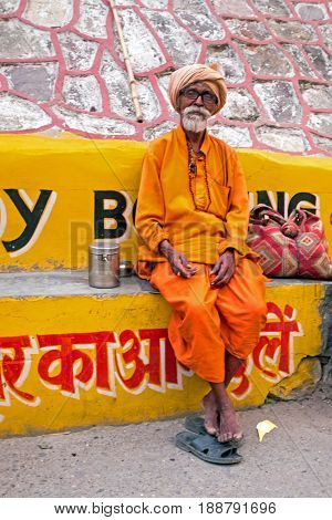 LAXMAN JHULA, INDIA - APRIL 19, 2017: A Hindu sadhu sitting in the streets in Laxman Jhula on the 19th april 2017 in India