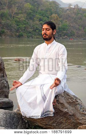 LAXMAN JHULA, INDIA - APRIL 19, 2017: A Hindu swami in white sitting on a rock at the holy river Ganges in Laxman Jhula on the 19th april 2017 in India