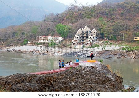 LAXMAN JHULA, INDIA - APRIL 23, 2017: People are doing puja in front of a shiva lingam at the  holy river Ganges in Laksman Jhula on the 23th april 2017 in India