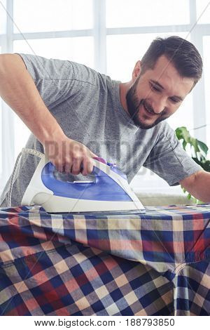 Vertical of caring man ironing diligently shirt on ironing board