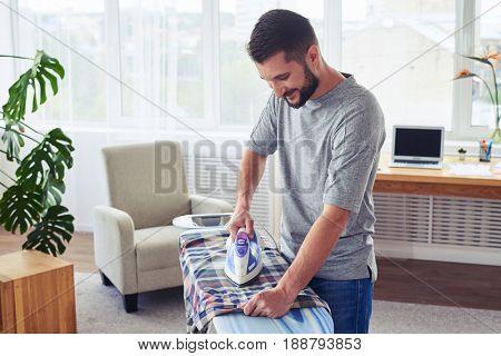 Mid shot of beautiful male ironing diligently shirt on ironing board