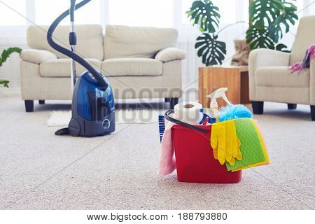 Wide shot of cleaning set in front of vacuum cleaner