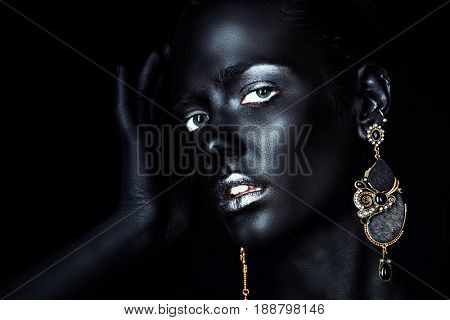Close-up portrait of a gorgeous young woman with perfect black skin and silver glitter lips wearing beautiful earrings. Cosmetics and make-up. Jewelry and bijouterie. African style.