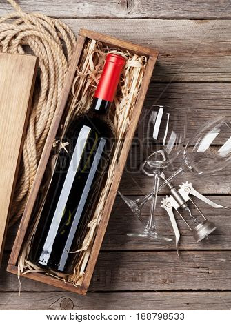 Red wine bottle and glasses on wooden table. Top view