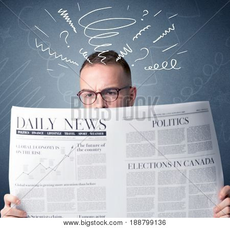 Confused businessman holding newspaper