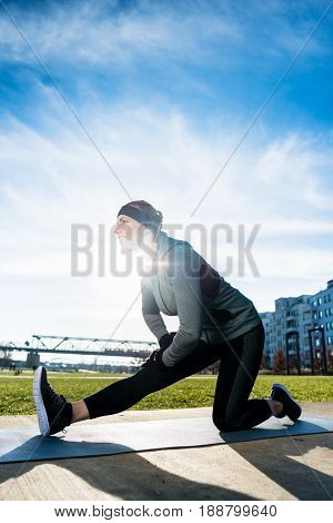 Low-angle view of a determined young woman stretching her leg while kneeling on a mat outdoors in summer