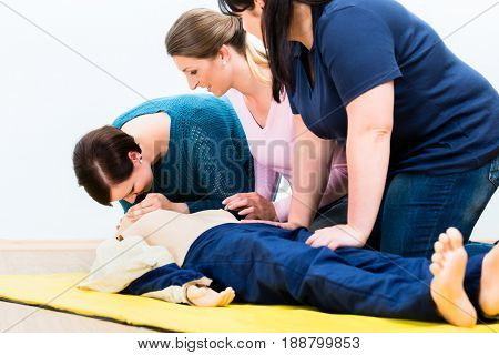 Group of women in first aid course exercising life-sustaining measures