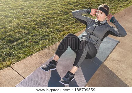 High-angle view of a determined young woman doing crunches for the abdominal muscles on a mat outdoors in a sunny day